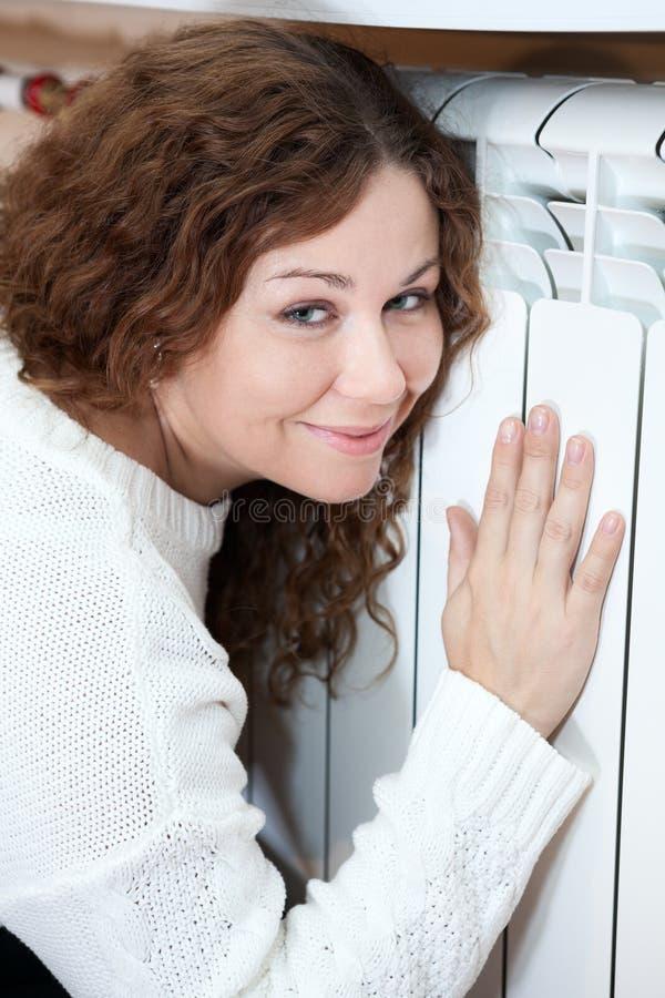 倾斜他的可爱的妇女对加热的幅射器 库存图片