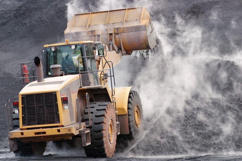 倾销矿物材料的前面装载者在堆 免版税库存图片
