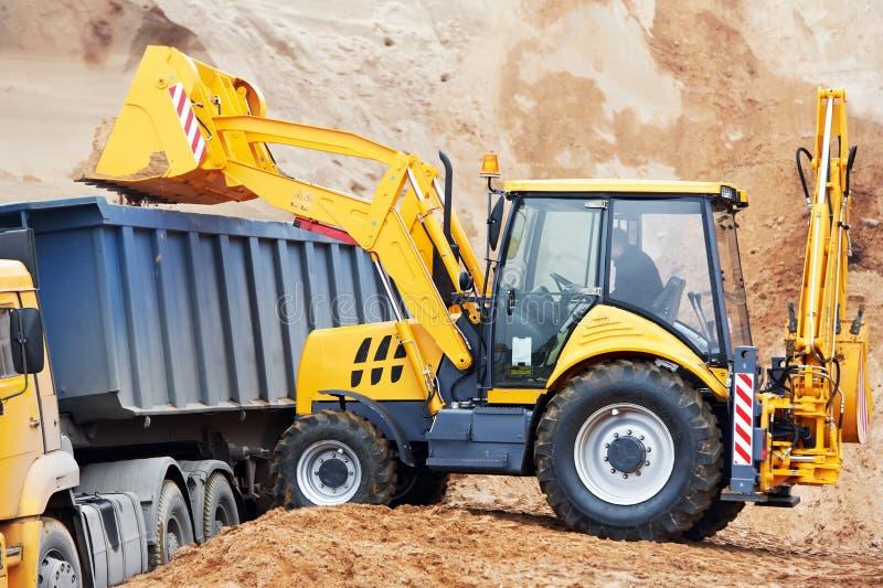倾销者挖掘机装入程序卸车轮子 库存照片