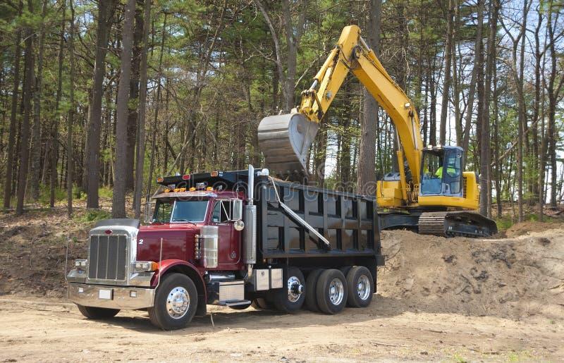 倾销者挖掘机装载卡车 免版税库存照片