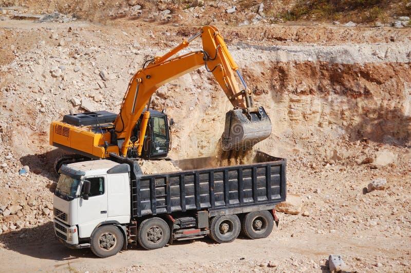 倾销者挖掘机装载沙子卡车 免版税图库摄影