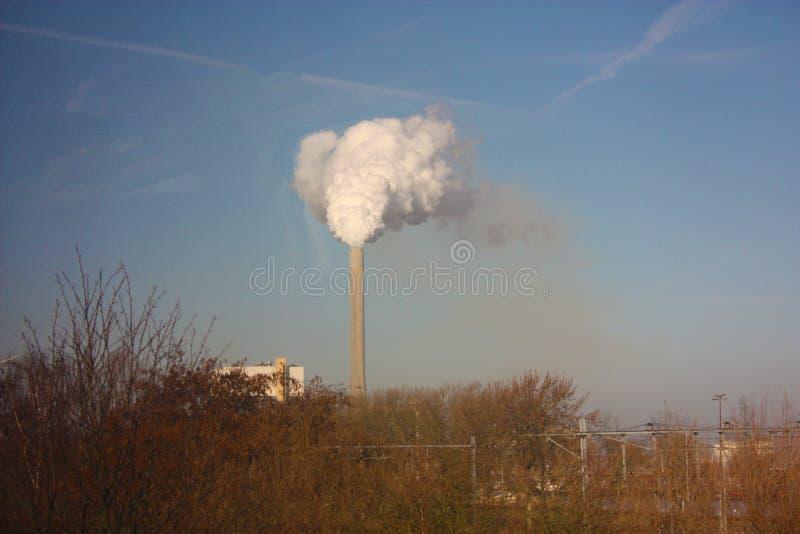 倾销遗骸工业处理成清楚的天空蔚蓝烟囱的出口,污染我们美丽的行星 库存照片