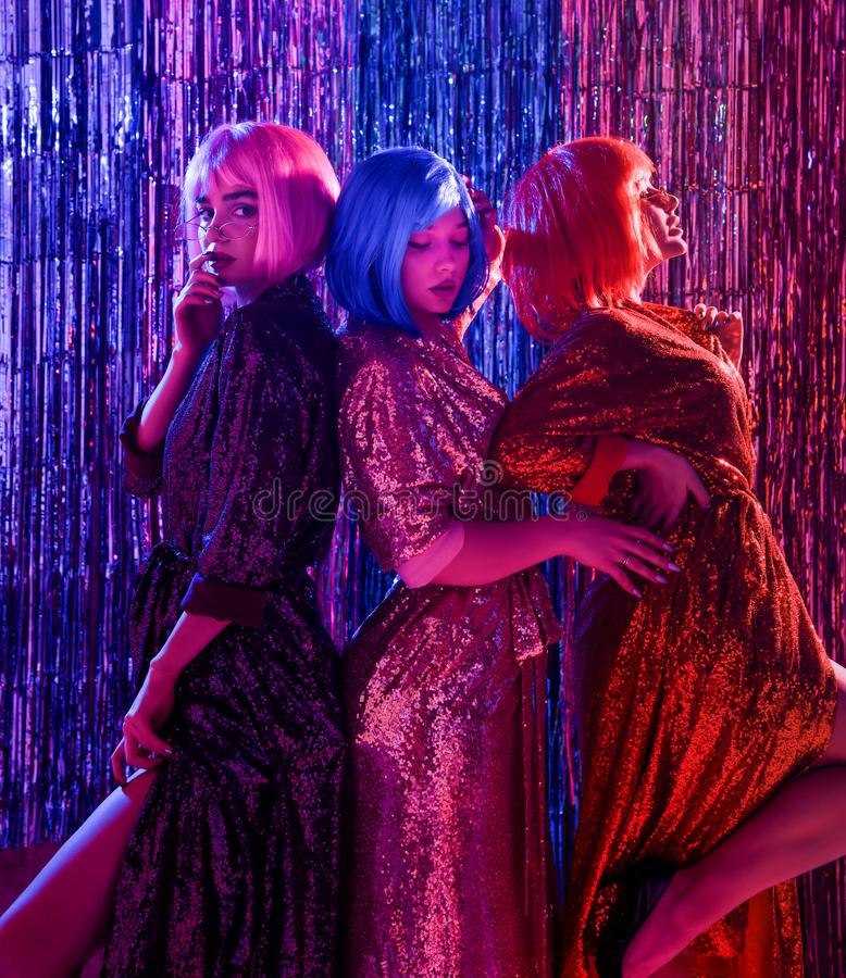 假发的女孩和有衣服饰物之小金属片的时髦的迷人的礼服,在迪斯科的霓虹灯 r 免版税库存照片