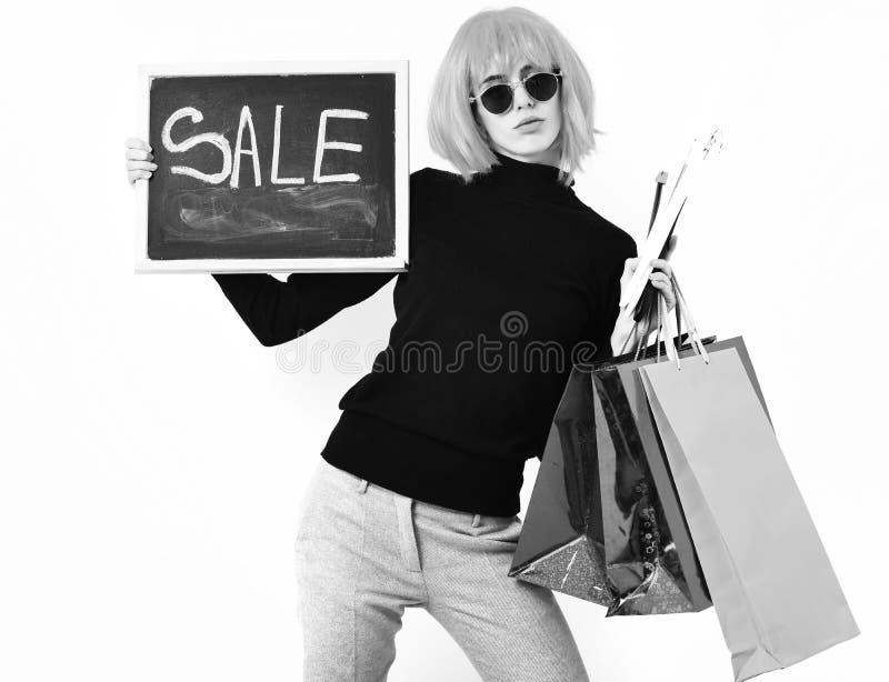 假发藏品包裹的,挂衣架,与销售题字的板女孩 免版税库存照片