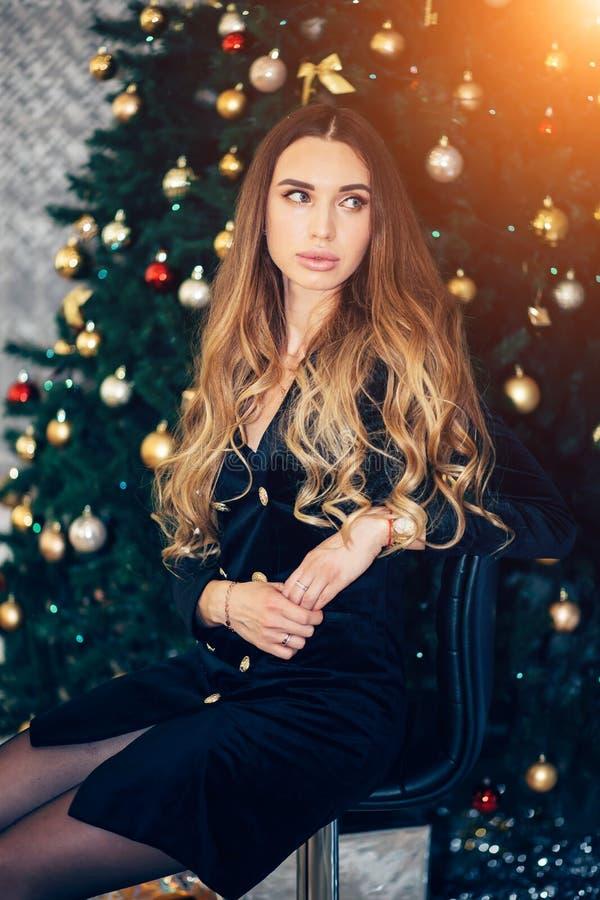 假日、庆祝和人概念-庄重装束的少妇在圣诞节内部背景 黑色礼服的女孩 免版税库存图片