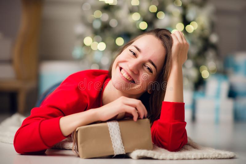 假日、庆祝和人概念-微笑的拖延金礼物盒的妇女佩带红色sweather的和牛仔裤 库存图片
