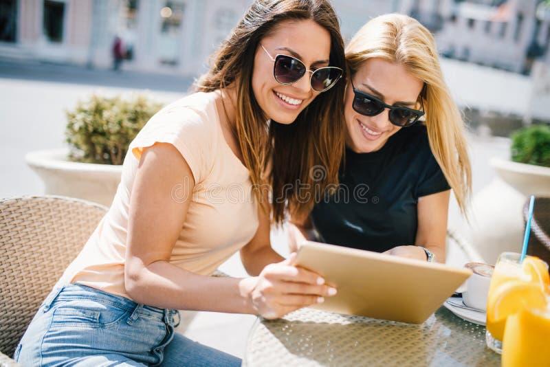 假日、旅游业和互联网-看在咖啡馆的美女平板电脑外面 库存照片