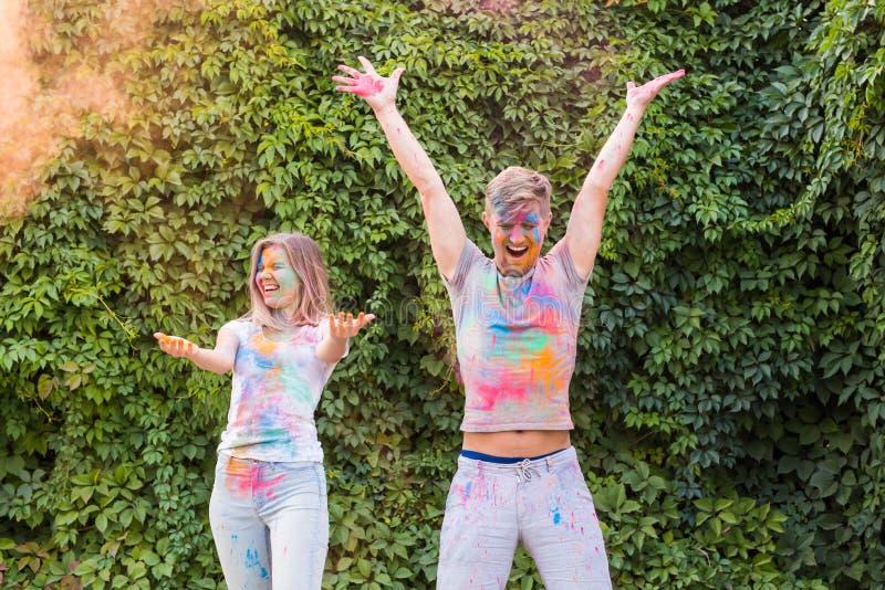 假日、holi和人概念-愉快的夫妇获得报道的乐趣在油漆 库存照片