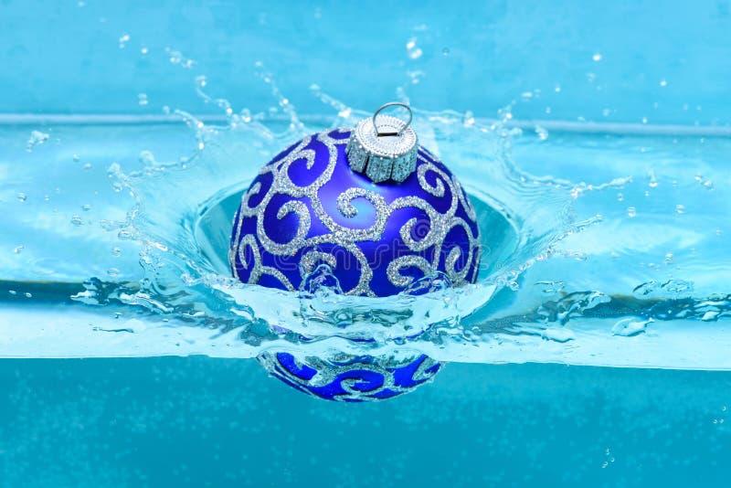 假日和假期概念 圣诞树的欢乐装饰,蓝色球被投下入水与飞溅,蓝色 免版税图库摄影