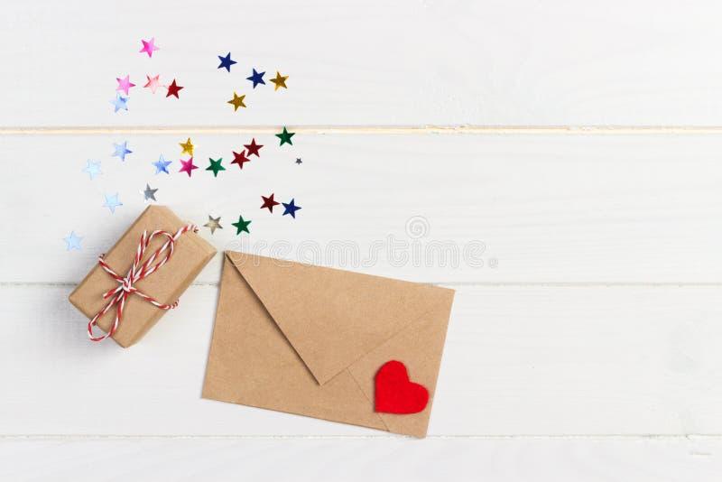 假日嘲笑:礼物盒、红色心脏和白纸在棕色信封在白色木背景 概念亲吻妇女的爱人 文本空间 免版税库存照片
