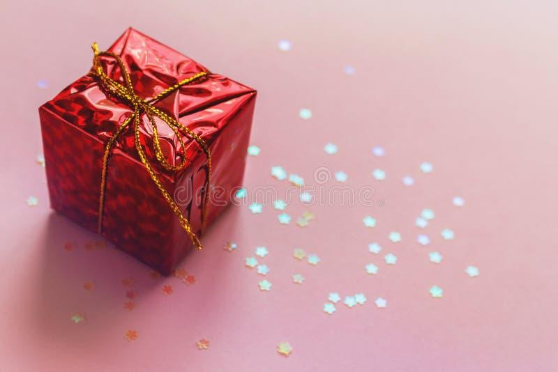 假日圣诞节贺卡 有金黄弓丝带的当前红色礼物盒在桃红色背景 免版税库存图片