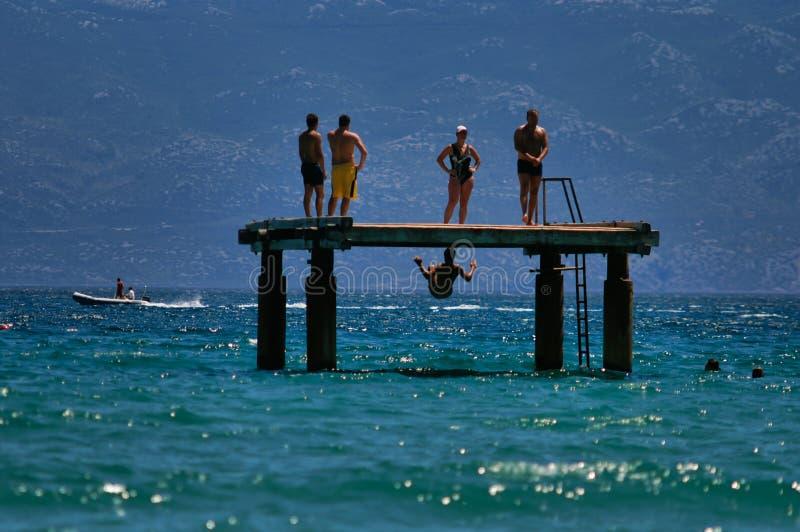 假日在克罗地亚,人跳进水 免版税库存图片