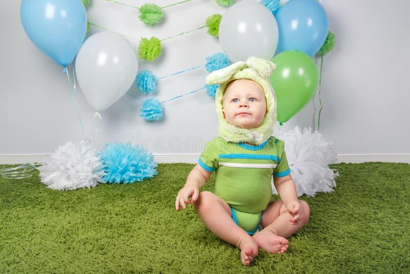 假日复活节兔子兔子服装的男婴有大耳朵的,穿戴以绿色给onesie穿衣,坐地毯 库存图片