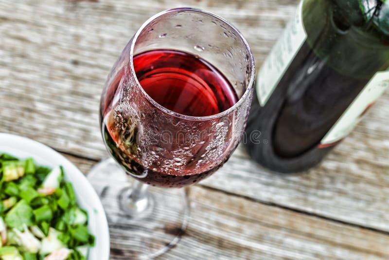 假日年轻酒 红葡萄酒用在背景的沙拉 概念:它` s博若莱红葡萄酒Nouveau时间 库存照片