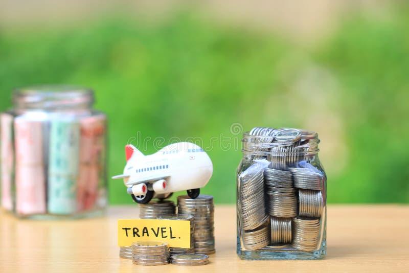 假日概念旅行预算,财政,堆硬币金钱在玻璃瓶和飞机的保存的计划有自然的 免版税库存照片