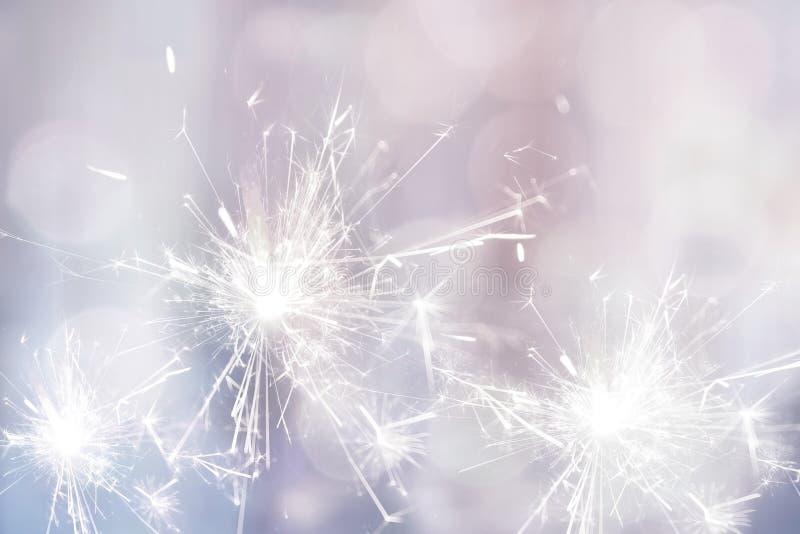 假日欢乐背景的白色闪烁发光物火 免版税图库摄影