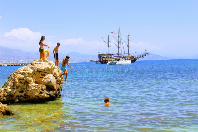 假日游客在一个巨大的岩石晒日光浴在海阿拉尼亚,土耳其 免版税库存图片