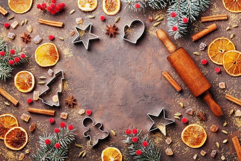 假日烘烤的姜饼曲奇饼的食物背景与切削刀、滚针和香料在台式视图 圣诞节食谱 免版税库存照片