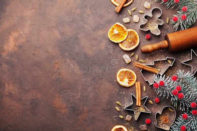 假日烘烤的曲奇饼的圣诞节背景与切削刀、滚针和香料在棕色台式视图 复制文本的空间 库存图片