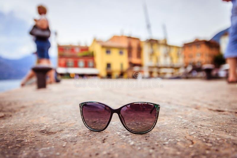 假日目的地:在地面,模糊的意大利村庄上的太阳镜在背景中 库存照片