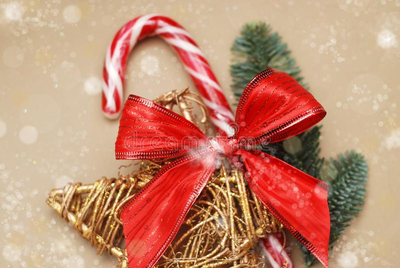 假日薄荷糖的背景图象忠心于红色弓和金黄装饰星和冷杉分支  免版税图库摄影