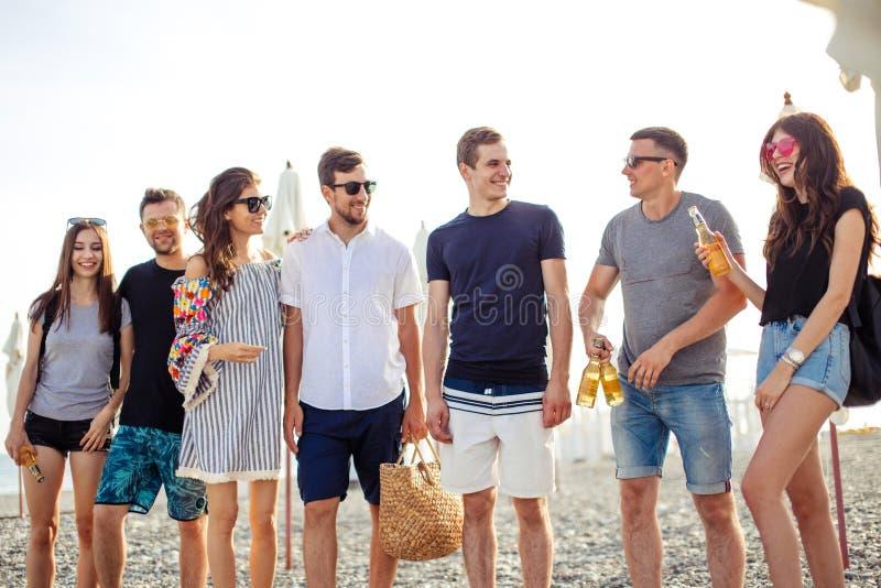 假日,假期 获得小组的朋友在海滩,走,饮料啤酒,微笑和拥抱的乐趣 库存图片