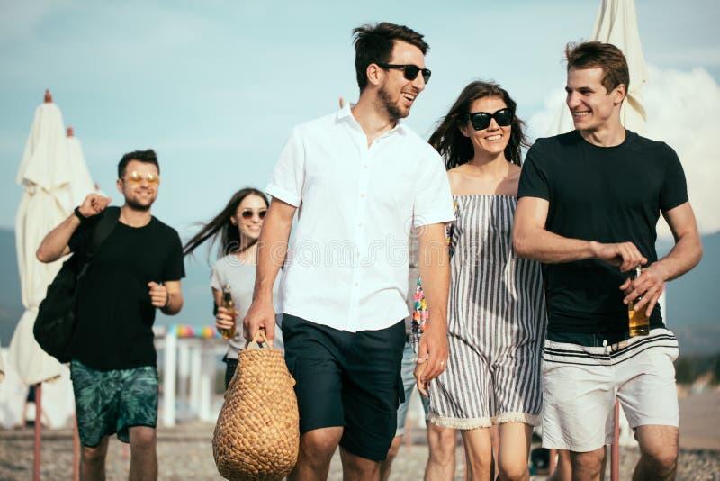 假日,假期 获得小组的朋友在海滩,走,饮料啤酒,微笑和拥抱的乐趣 免版税图库摄影