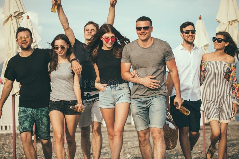 假日,假期 获得小组的朋友在海滩,走,饮料啤酒,微笑和拥抱的乐趣 免版税库存照片
