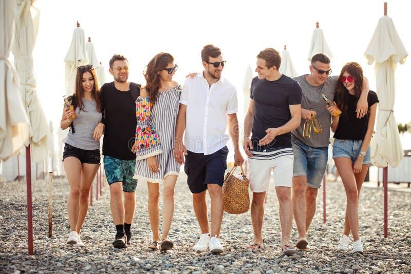 假日,假期 获得小组的朋友在海滩,走,饮料啤酒,微笑和拥抱的乐趣 免版税库存图片