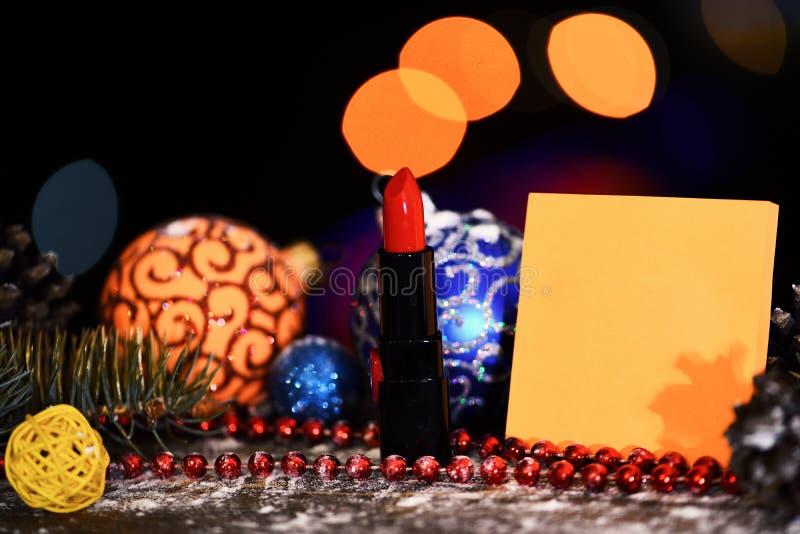 假日xmas装饰五颜六色的玩具或球与defocused bokeh光和唇膏在五颜六色的背景,拷贝spac 免版税库存图片