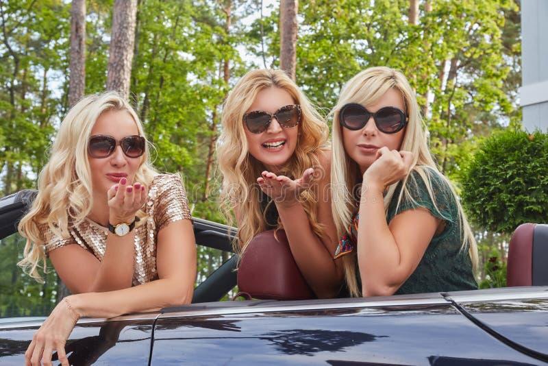 假期和人概念 穿在太阳镜的三个愉快的白肤金发的女性朋友流行的服装做空气亲吻 库存照片