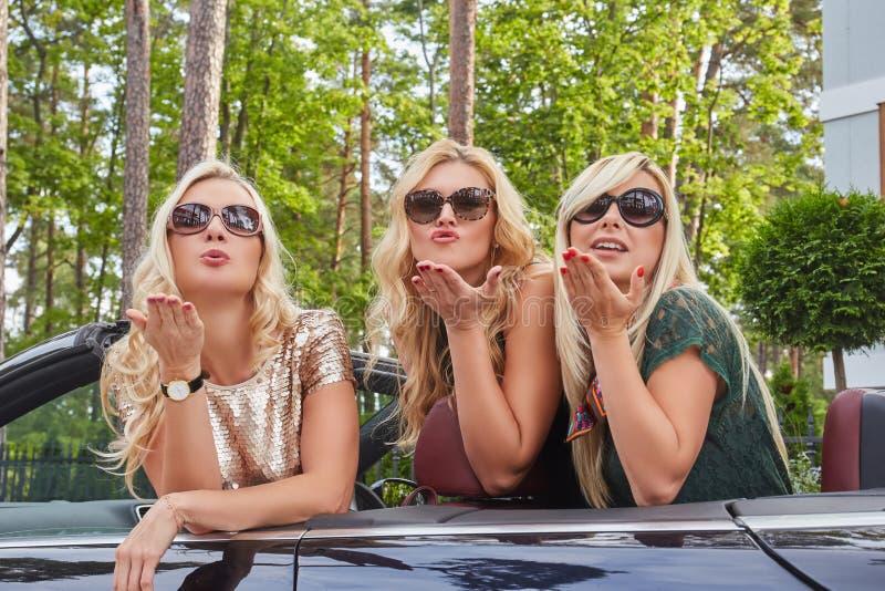 假期和人概念 穿在太阳镜的三个愉快的白肤金发的女性朋友流行的服装做空气亲吻 免版税图库摄影