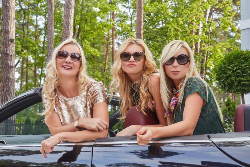 假期和人概念 穿在太阳镜的三个愉快的白肤金发的女性朋友流行的服装坐在a 免版税库存照片