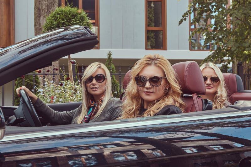 假期和人概念 穿在太阳镜的三个白肤金发的女性朋友流行的服装坐在a 免版税图库摄影