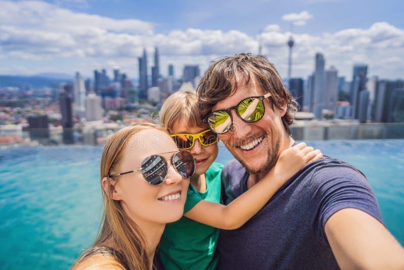 假期和技术 有一起采取selfie的孩子的幸福家庭在游泳场附近有全景  免版税库存图片