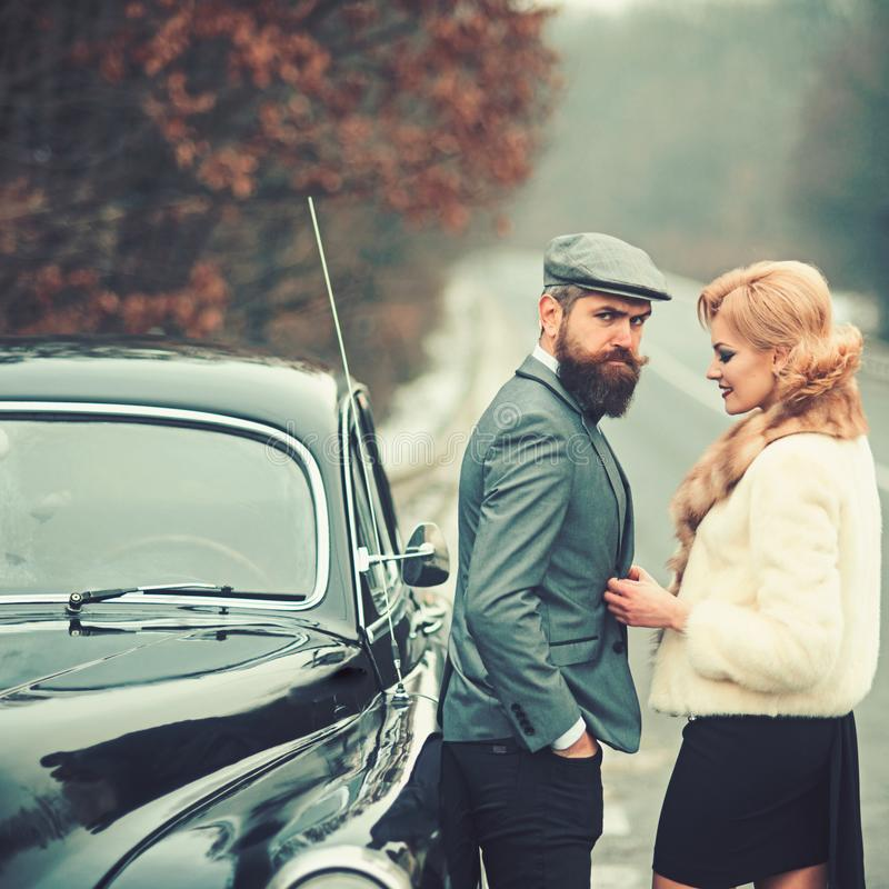 假期和旅行的概念 夫妇的假期在爱的在减速火箭的汽车 免版税库存图片