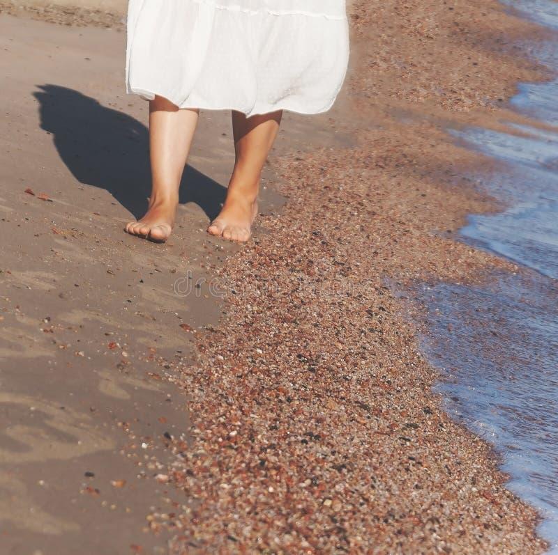 假期旅行-妇女走在白色沙子relaxi的腿特写镜头 免版税库存图片