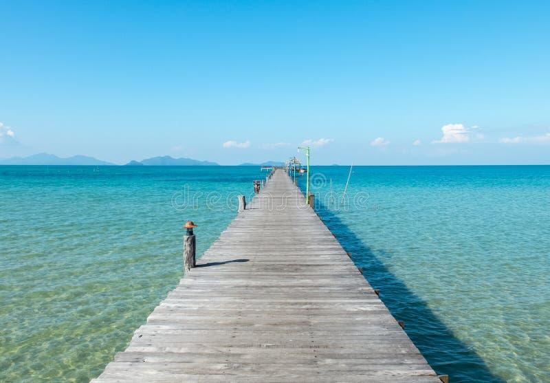 假期概念、木道路透明的蓝色海之间和天空从海滩海岛码头的在泰国 免版税库存照片