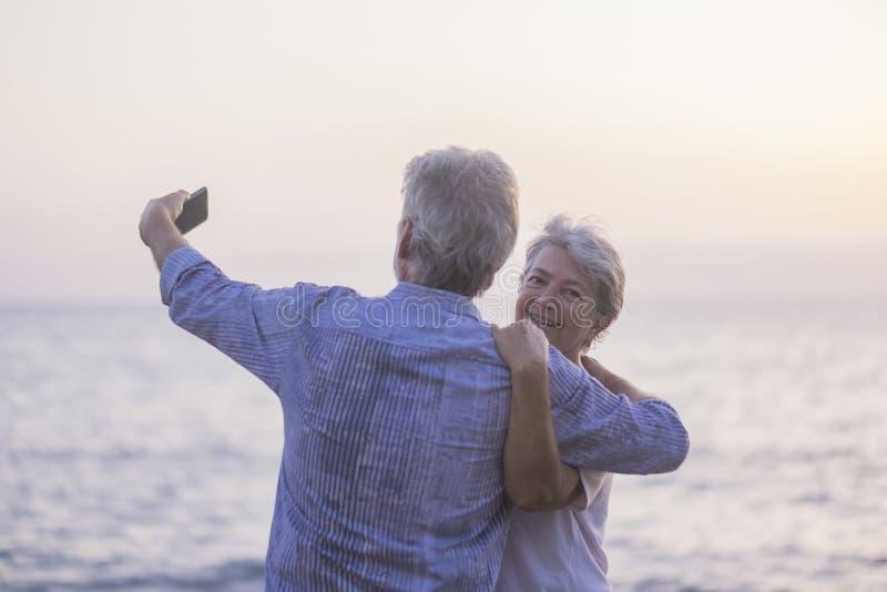 假期的概念,技术、旅游业、旅行和人们-愉快的资深加上在Pebble海滩笑的手机电话 库存照片