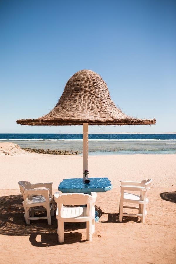 假期节假日 在帐篷下的三张海滩躺椅在海滩 免版税库存图片
