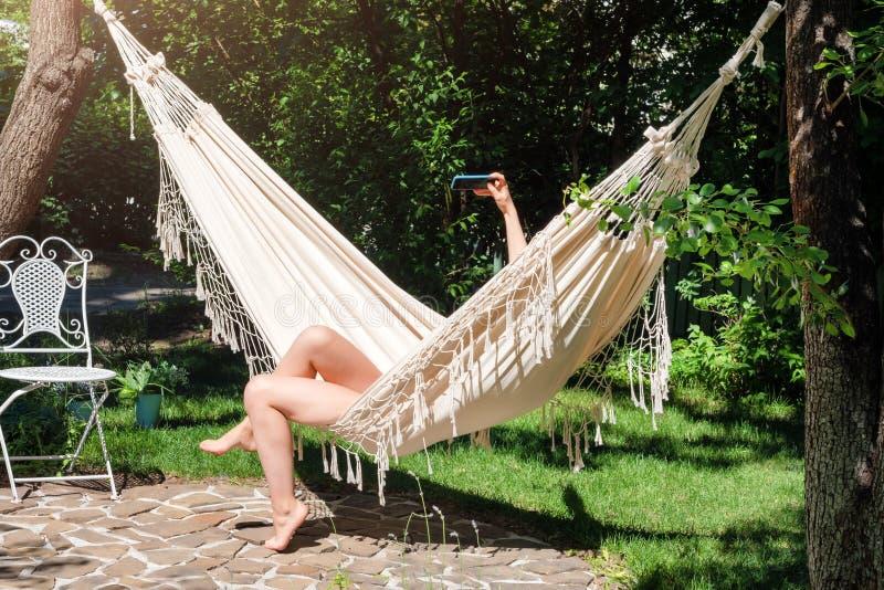 假期Selfie 享受夏天 使用智能手机的少妇放置在吊床在庭院里 免版税库存照片