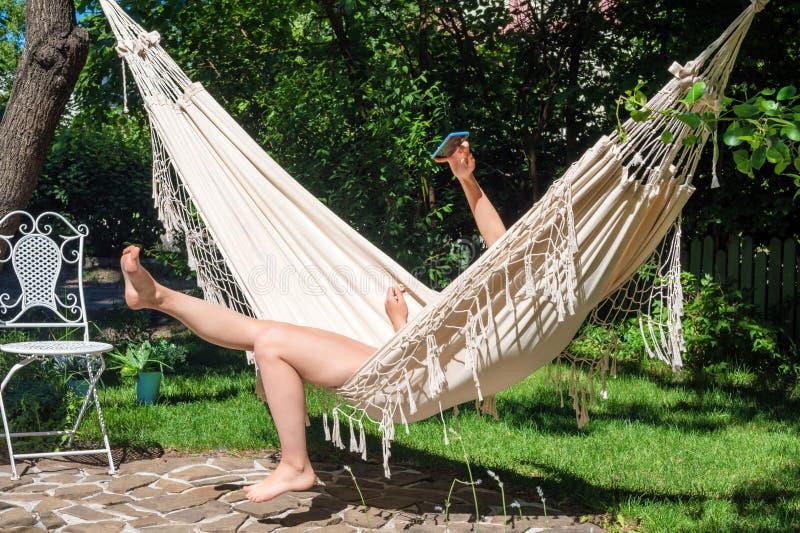 假期Selfie 享受夏天 使用智能手机的少妇放置在吊床在庭院里 免版税图库摄影