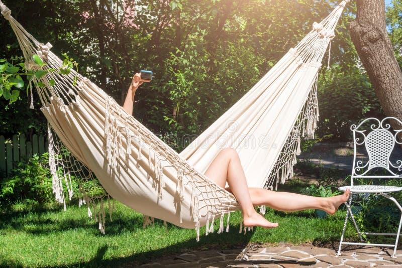 假期Selfie 享受夏天 使用智能手机的少妇放置在吊床在庭院里 免版税库存图片