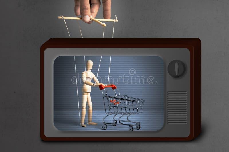 假电视新闻 对买家的行为的控制 有购物的台车的人从象玩偶的超级市场由操纵傀儡的人 免版税库存照片