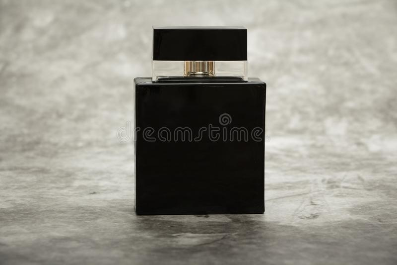 假装一个黑瓶在砖灰色墙壁背景的人的香水 安置文本 免版税库存照片