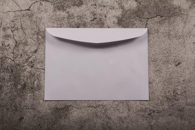 假装一张模板桌与一个空白的信封,笔记薄和与文具在灰色背景中 在视图之上 平的位置 免版税库存照片