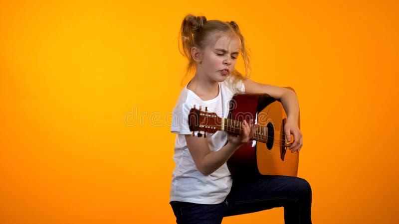 假装可爱的青少年的女孩弹吉他,梦想成为著名摇滚明星 库存图片