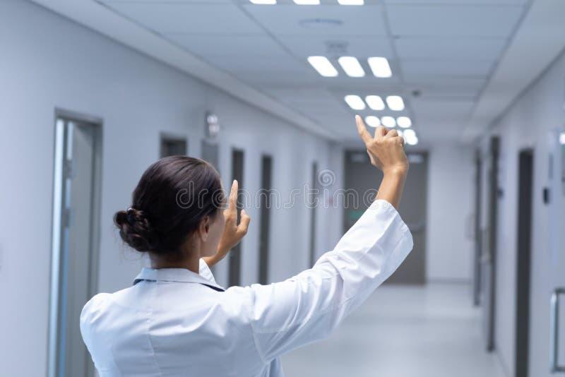 假装女性的医生在医院接触在走廊的一个无形的屏幕 图库摄影