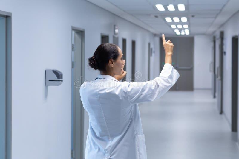 假装女性的医生在医院接触在走廊的一个无形的屏幕 免版税图库摄影