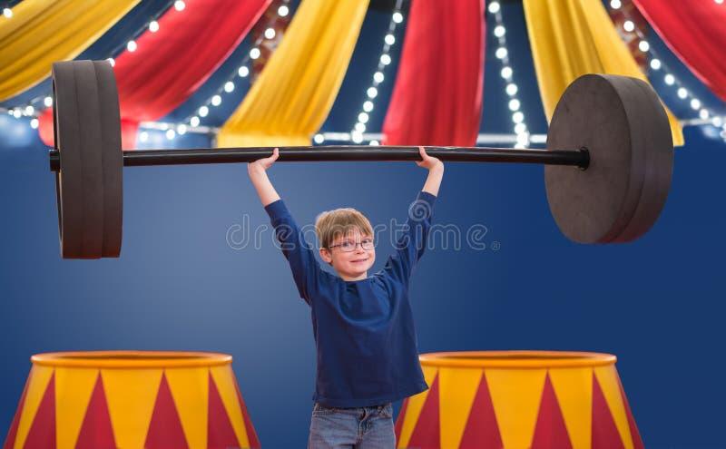 假装年轻的男孩是大力士举大杠铃的马戏团演员 免版税库存图片
